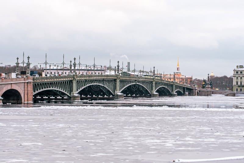 Γέφυρα τριάδας στη Αγία Πετρούπολη πέρα από τον παγωμένο ποταμό χειμερινού Neva στοκ φωτογραφίες