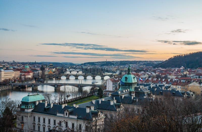 Γέφυρες της Πράγας, ποταμός Vltava, κόκκινες στέγες πανοράματος ηλιοβασιλέματος πόλεων και πολύχρωμοι τοίχοι, τσεχικά στοκ εικόνα