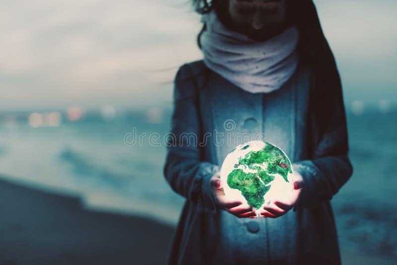 Γήινη σφαίρα που καίγεται στα χέρια της γυναίκας στην παραλία τη νύχτα στοκ εικόνες