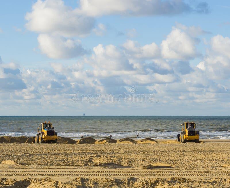 Γήινοι μετακινούμενοι που εργάζονται στις μηχανές εξοπλισμού τους στην παραλία για τη συντήρηση που κινεί την άμμο στοκ φωτογραφίες