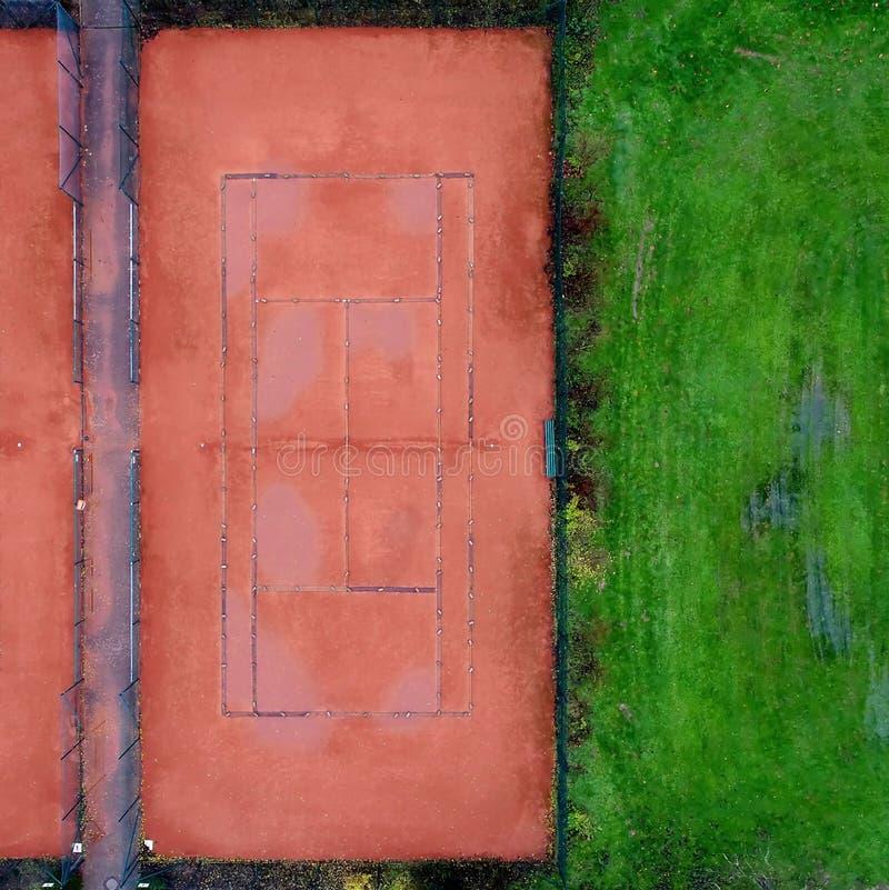 Γήπεδο αντισφαίρισης με το κόκκινο αμμοχάλικο δίπλα σε έναν χορτοτάπητα, αφηρημένη επίδραση κοντά στοκ φωτογραφίες με δικαίωμα ελεύθερης χρήσης