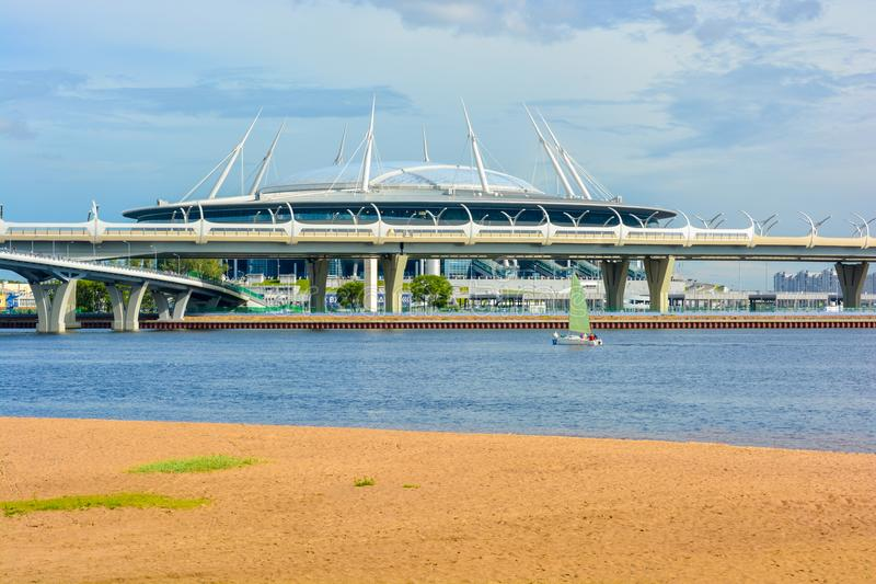 Γήπεδο ποδοσφαίρου αποκορυφώματος σταδίων Αγίου Πετρούπολη στο νησί Krestovsky πίσω από τη γέφυρα και τον κόλπο στοκ φωτογραφία με δικαίωμα ελεύθερης χρήσης