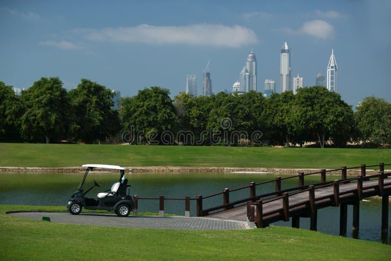 γήπεδο του γκολφ στο Ντουμπάι με τους φοίνικες και ουρανοξύστες στο υπ στοκ φωτογραφίες με δικαίωμα ελεύθερης χρήσης
