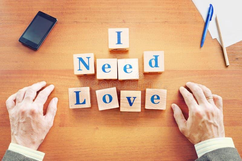 Χρειάζομαι την αγάπη Γίνοντα επιχειρηματίας κείμενο από τους ξύλινους κύβους ελεύθερη απεικόνιση δικαιώματος