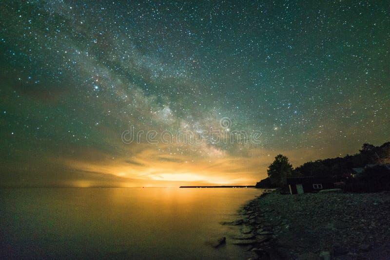 Γαλακτώδεις τρόπος και αστέρια πέρα από τη λίμνη που παρουσιάζει την ακτή και απότομους βράχους α στοκ φωτογραφία