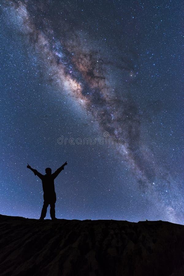 Γαλακτώδες τοπίο τρόπων Σκιαγραφία του ευτυχούς ατόμου που στέκεται πάνω από το βουνό με το νυχτερινό ουρανό και του έξυπνου αστε στοκ φωτογραφίες