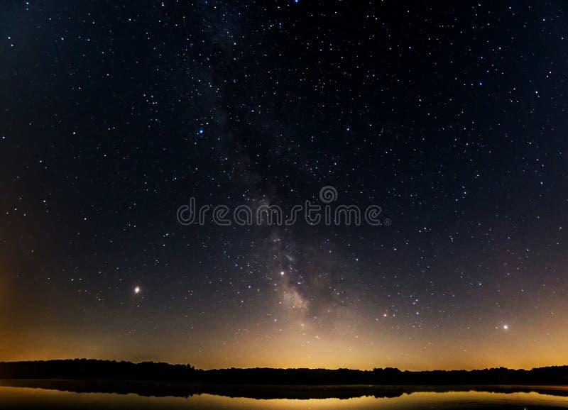 Γαλακτώδης γαλαξίας τρόπων γεμισμένη στην αστέρι νύχτα πέρα από τη λίμνη στοκ εικόνα