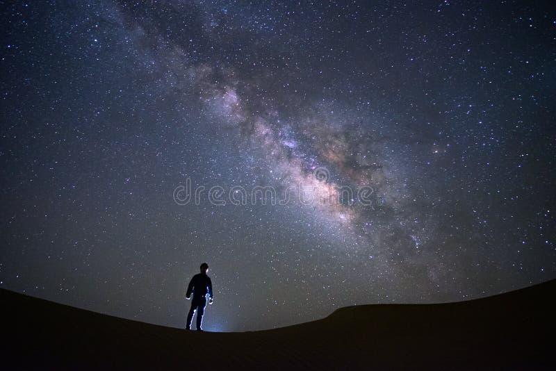 Γαλακτώδης γαλαξίας τρόπων με ένα άτομο που στέκεται και που προσέχει στην έρημο πίσσας, Jaisalmer, Ινδία στοκ φωτογραφία