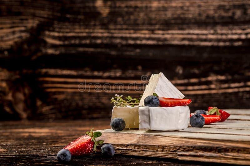 Γαλλική λιχουδιά Κομψό Camembert Μαλακό τυρί με την άσπρη φόρμα με τα άγρια μούρα Στρογγυλό Camembert με τις φράουλες και στοκ φωτογραφίες