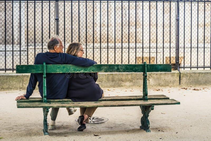 Γαλλική συνεδρίαση ζευγών σε έναν πάγκο στοκ εικόνα με δικαίωμα ελεύθερης χρήσης