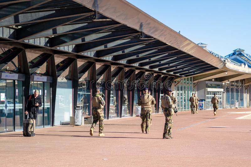 Γαλλικοί στρατιώτες στο πλήρες εργαλείο, που οπλίζονται με τα τουφέκια, στην περίπολο στο διεθνή αερολιμένα της Λυών Άγιος Exuper στοκ εικόνες