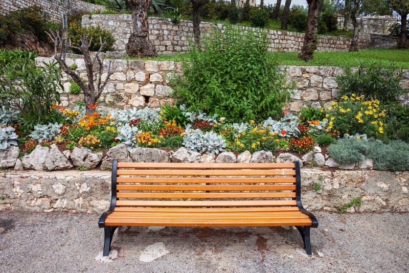 Γαλλικός κήπος Riviera με τα λουλούδια και τον πάγκο στοκ εικόνες