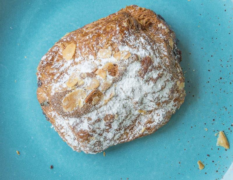 Γαλλικός croissant με τα αμύγδαλα και γυαλί sucre στο μπλε πιάτο στοκ φωτογραφίες με δικαίωμα ελεύθερης χρήσης