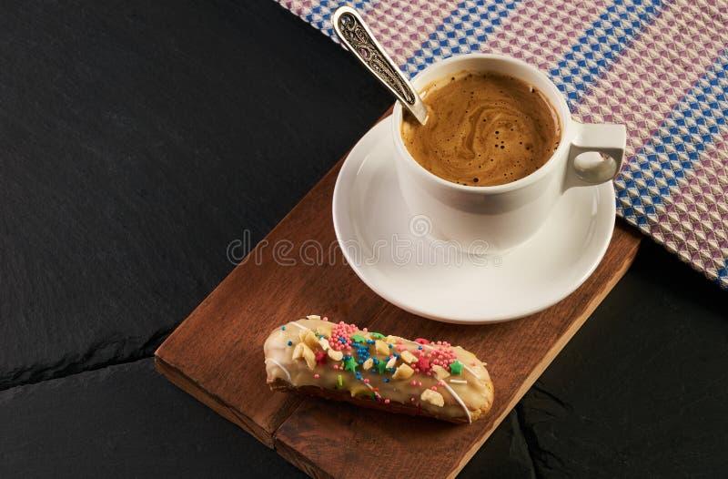Γαλλικό κρεμώδες ECLAIR και καυτό φλυτζάνι καφέ στοκ φωτογραφίες
