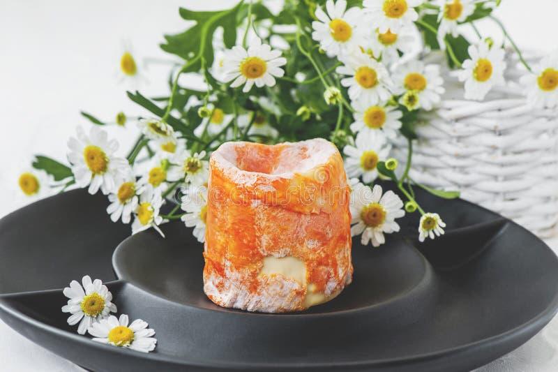 Γαλλικό μαλακό τυρί με τον άσπρο πορτοκαλή φλοιό φορμών epoisses σε ένα μαύρο πιάτο μεταλλινών o στοκ εικόνα με δικαίωμα ελεύθερης χρήσης