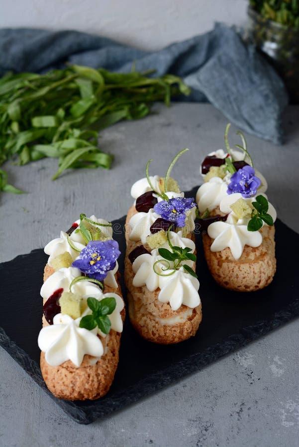 Γαλλικό ECLAIR με την κρέμα φρούτων και καρύδων και ευγενές mousse εύγευστο επιδόρπιο Κέικ στο λούστρο Προϊόν βιομηχανιών ζαχαρωδ στοκ φωτογραφίες με δικαίωμα ελεύθερης χρήσης