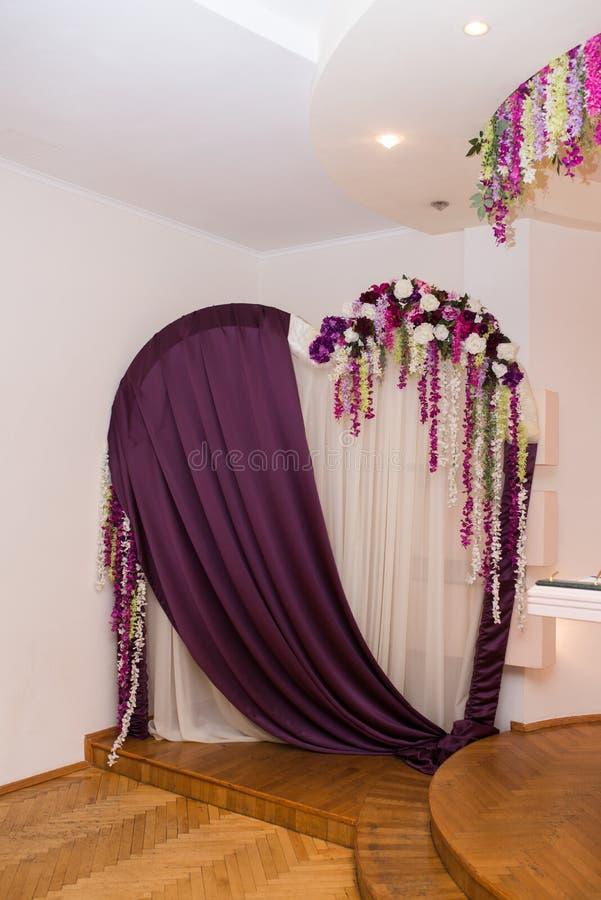 Γαμήλια αψίδα με μορφή μιας καρδιάς που διακοσμείται με το πορφυρά και άσπρα υλικό και τα λουλούδια Floral αψίδα σε μια γαμήλια τ στοκ φωτογραφία με δικαίωμα ελεύθερης χρήσης