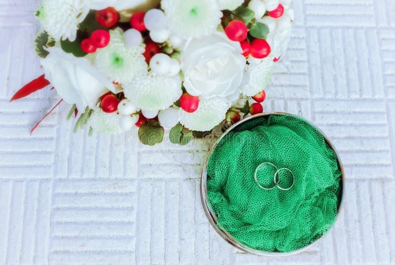Γαμήλια δαχτυλίδια αρραβώνων με τα λουλούδια στοκ φωτογραφία