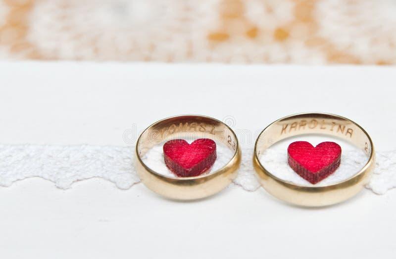 Γαμήλια δαχτυλίδια και κόκκινες καρδιές ενός πολωνικού παντρεμένου ζευγαριού στοκ φωτογραφία