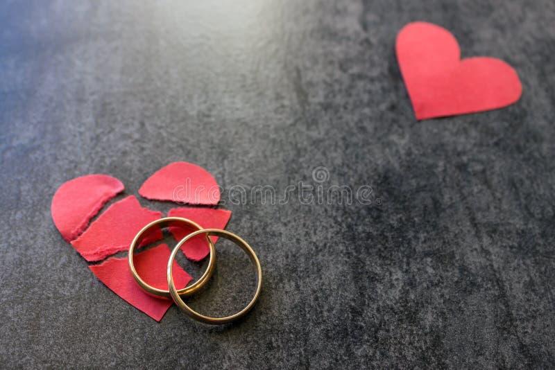 Γαμήλια δαχτυλίδια και σπασμένη κόκκινη καρδιά Μαύρη ανασκόπηση Το conce στοκ εικόνα με δικαίωμα ελεύθερης χρήσης