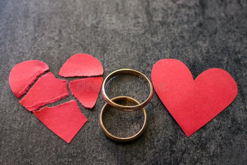 Γαμήλια δαχτυλίδια και σπασμένη κόκκινη καρδιά Μαύρη ανασκόπηση Το conce στοκ εικόνες με δικαίωμα ελεύθερης χρήσης