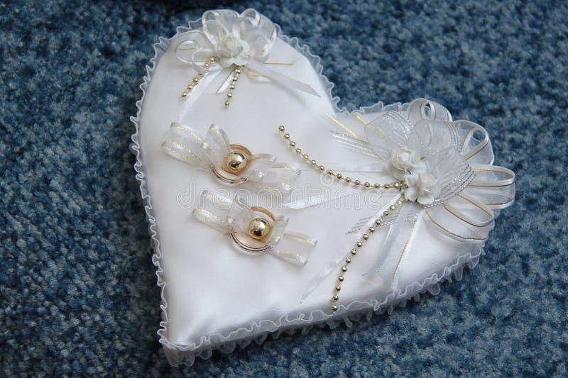 Γαμήλια δαχτυλίδια σε ένα άσπρο μικρό μαξιλάρι σε ένα μπλε υπόβαθρο στοκ φωτογραφία με δικαίωμα ελεύθερης χρήσης
