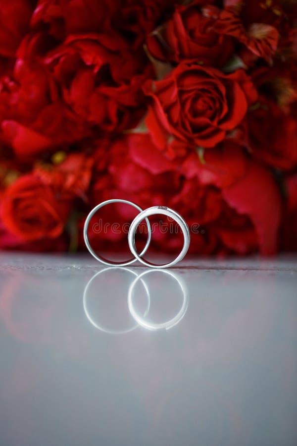 Γαμήλια δαχτυλίδια στο κόκκινο υπόβαθρο λουλουδιών r στοκ φωτογραφίες