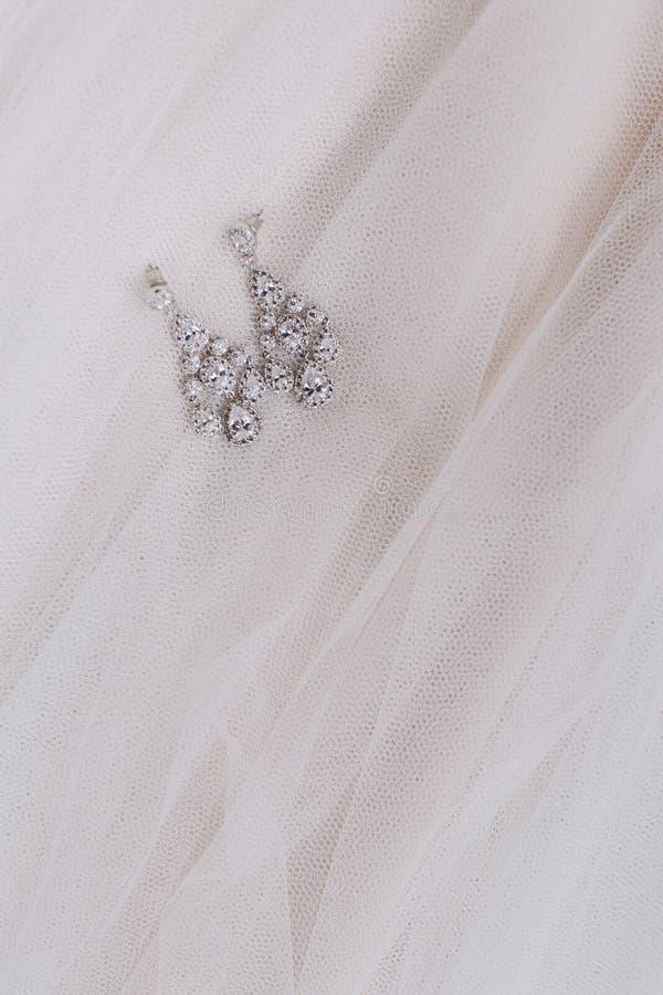Γαμήλια εξαρτήματα πολυτέλειας για τη νύφη Νυφικά earings στο viel διάστημα αντιγράφων Τοπ όψη στοκ εικόνα