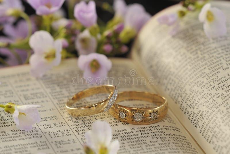 Γαμήλια ζώνες, Βίβλος και λουλούδια στοκ εικόνα