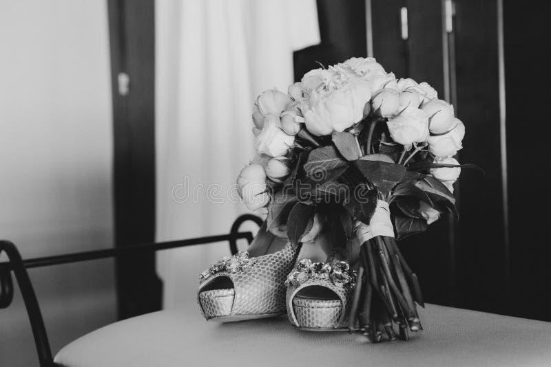 Γαμήλια παπούτσια και γαμήλια ανθοδέσμη, γραπτά στοκ εικόνες