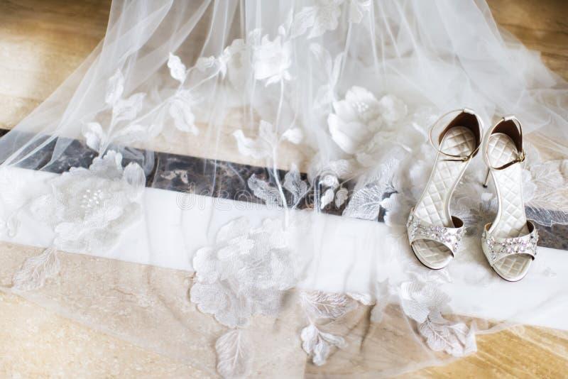 Γαμήλια παπούτσια με τα κοσμήματα στο νυφικό πέπλο στοκ εικόνες