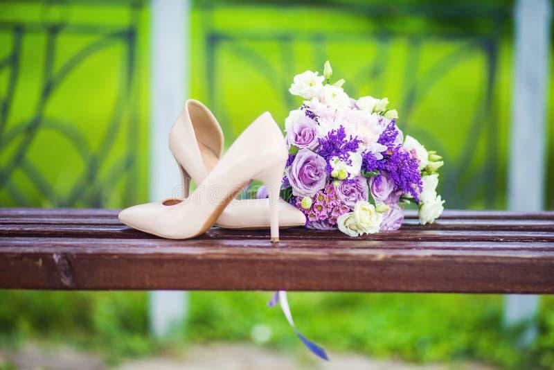 Γαμήλια παπούτσια με την κομψή ανθοδέσμη νυφών ` s στοκ φωτογραφία