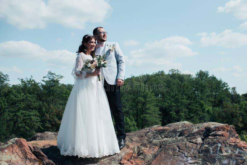Γαμήλια φωτογραφία ενός γενειοφόρου νεόνυμφου με τα γυαλιά σε ένα γκρίζο σακάκι και μια νύφη σε έναν βράχο στοκ εικόνες