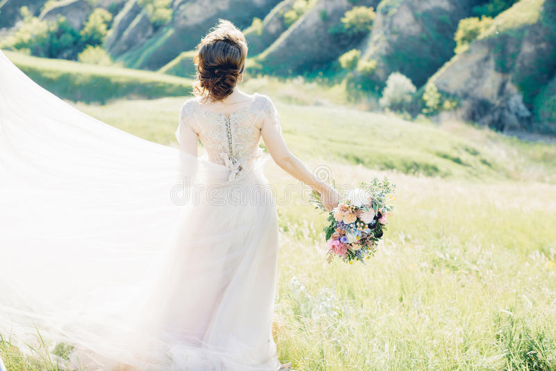 Γαμήλια φωτογραφία Καλών Τεχνών Όμορφη νύφη με την ανθοδέσμη και φόρεμα με το τραίνο στη φύση στοκ εικόνες