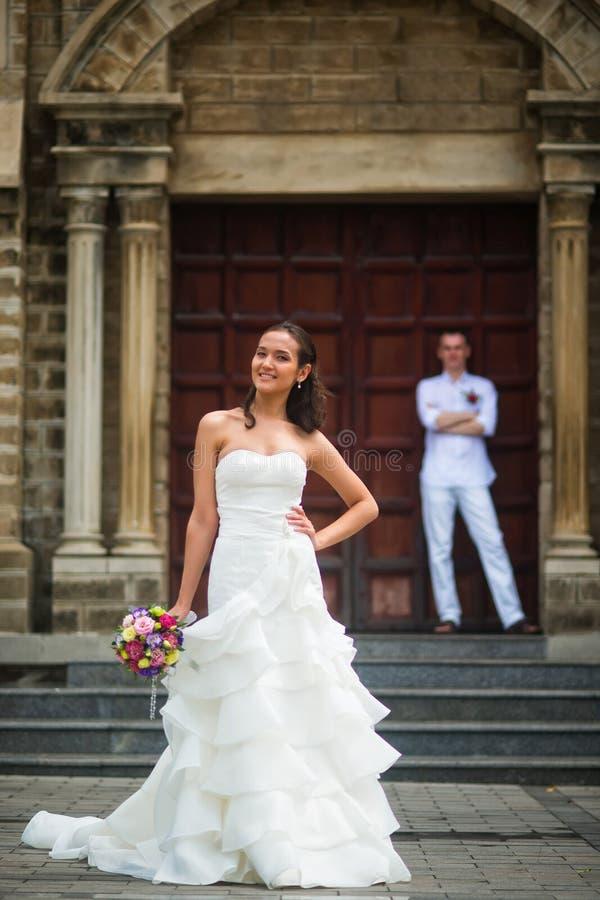 Γαμήλια φωτογραφία με τη νύφη και το νεόνυμφο Όμορφη τοποθέτηση νυφών στα πλαίσια του νεόνυμφου και της καθολικής εκκλησίας στοκ εικόνες