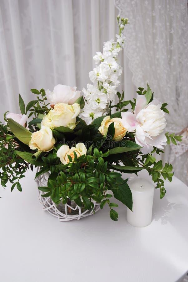 Γαμήλια floral ρύθμιση Ζωηρόχρωμη ακόμα ζωή με τα τριαντάφυλλα στο βάζο γυαλιού με το άσπρο υπόβαθρο Επιτραπέζια διακόσμηση κόμμα στοκ φωτογραφία