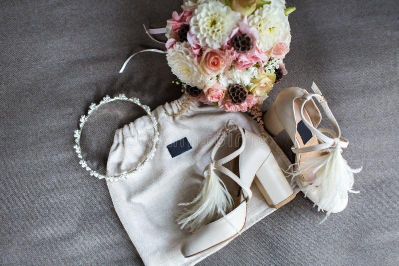 Γαμήλιες παπούτσια, τιάρα και ανθοδέσμη σε ένα γκρίζο υπόβαθρο στοκ εικόνα
