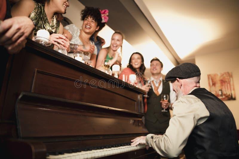 Γαμήλιοι φιλοξενούμενοι που έχουν τη διασκέδαση με το πιάνο στοκ εικόνες με δικαίωμα ελεύθερης χρήσης
