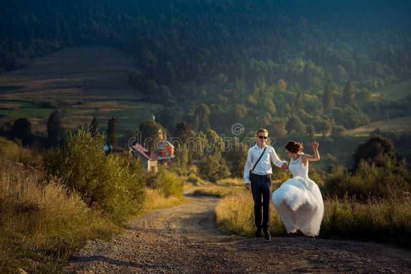 Γαμήλιος πυροβολισμός χαρούμενου του ελκυστικού που παντρεύτηκε ακριβώς στο χορεύοντας ο nthe δρόμο γυαλιών ηλίου στο υπόβαθρο τω στοκ φωτογραφία με δικαίωμα ελεύθερης χρήσης