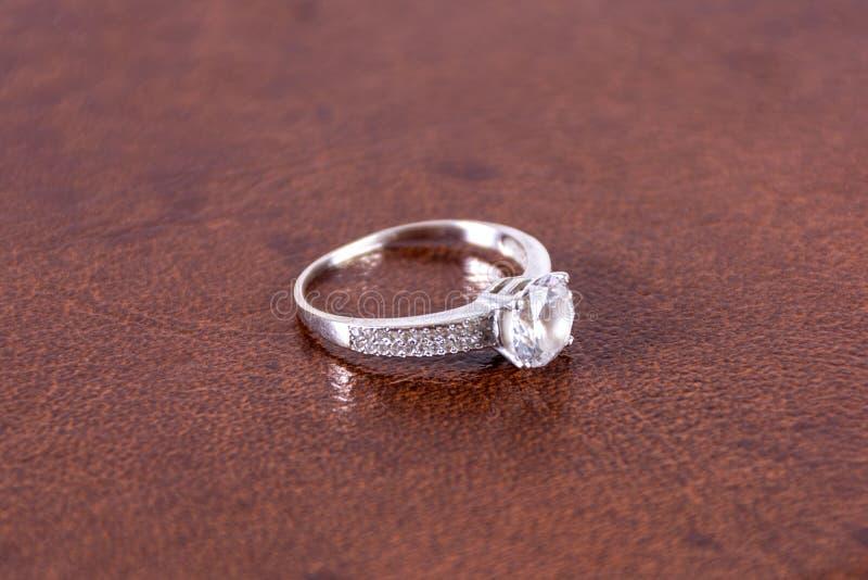 Γαμήλιο δαχτυλίδι δέσμευσης διαμαντιών ασημένιο στο καφετί θολωμένο και μαλακό υπόβαθρο δέρματος στοκ εικόνες