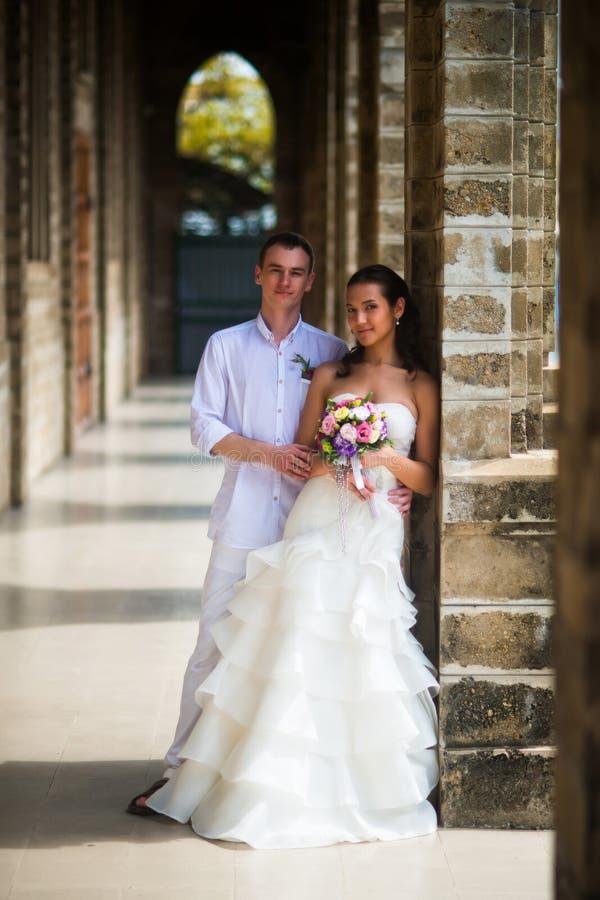 Γαμήλιο ζεύγος που στέκεται στη στοά της καθολικής εκκλησίας στοκ εικόνα