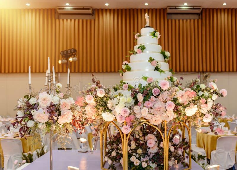 Γαμήλιο κέικ με διακοσμημένος με τα λουλούδια και το κηροπήγιο στην τελετή γάμου στοκ εικόνες