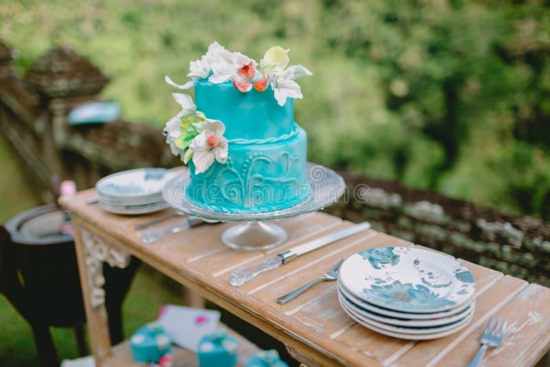 Γαμήλιο νόστιμο κέικ με τα λουλούδια και τα δώρα στοκ εικόνα