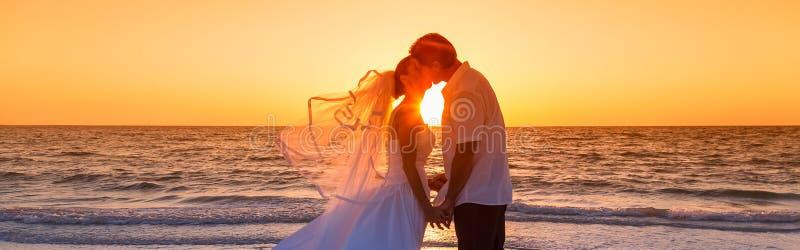 Γαμήλιο πανόραμα παραλιών ηλιοβασιλέματος παντρεμένου ζευγαριού νυφών και νεόνυμφων στοκ εικόνες