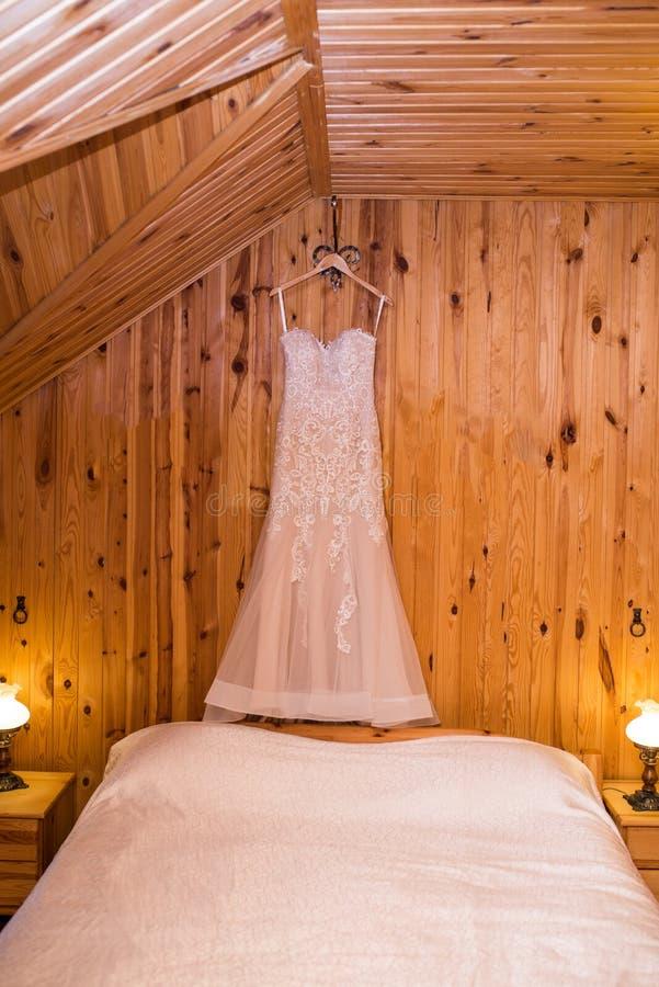 Γαμήλιο φόρεμα γαμήλιας μπεζ κομψότητας στην κρεμάστρα σε έναν ξύλινο τοίχο όμορφη εσθήτα Weding στοκ εικόνες με δικαίωμα ελεύθερης χρήσης
