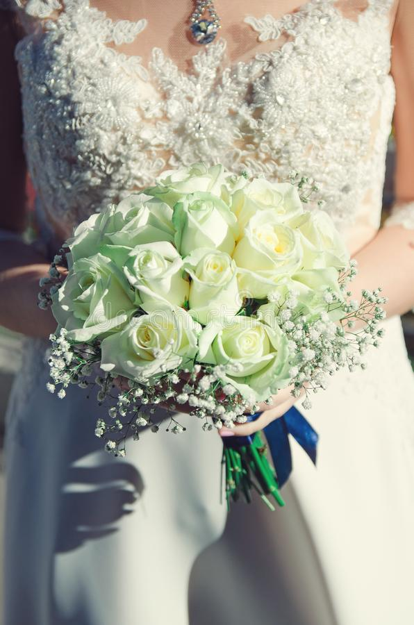 Γαμήλιο φόρεμα και νυφική ανθοδέσμη των άσπρων τριαντάφυλλων Κάθετη φωτογραφία στοκ εικόνα