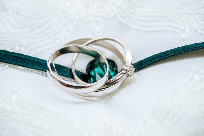 Γαμήλια άσπρος-χρυσά δαχτυλίδια με το διαμάντι και τη σμαραγδένια κορδέλλα στοκ εικόνα