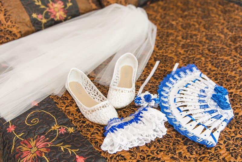 Γαμήλια ανθοδέσμη και παπούτσια της νύφης Garter, παπούτσια, ανεμιστήρας, νύφη πέπλων στο κρεβάτι στοκ εικόνα με δικαίωμα ελεύθερης χρήσης
