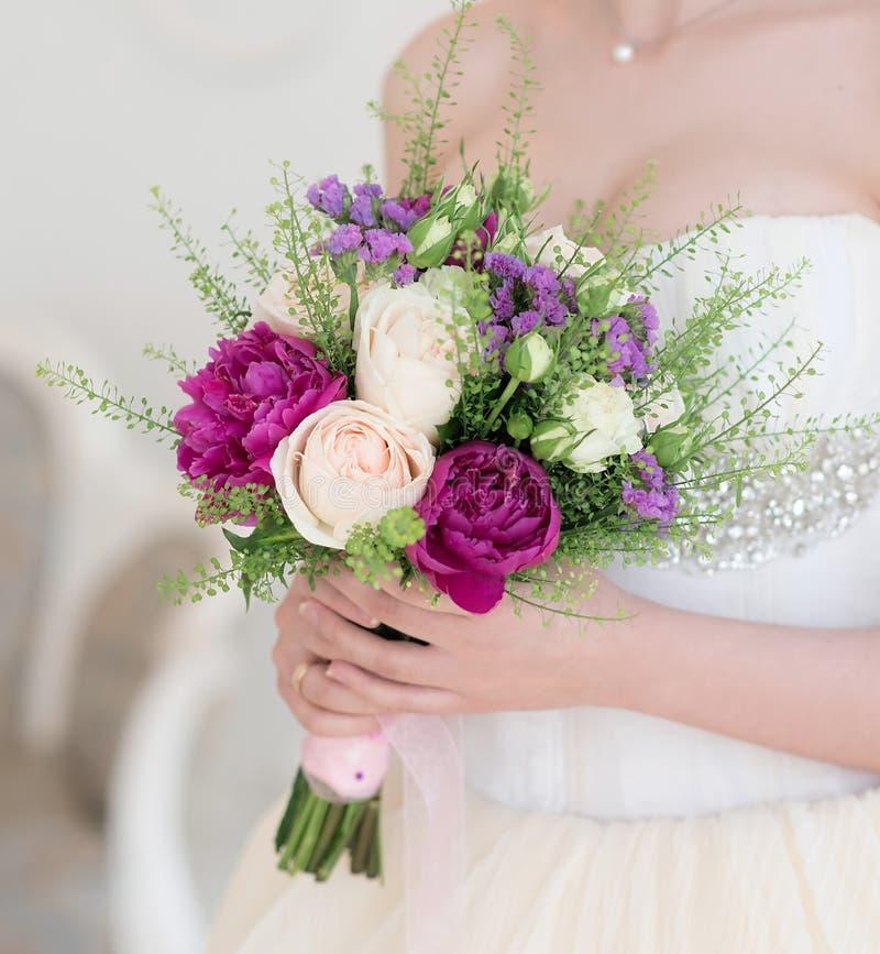 Γαμήλια ανθοδέσμη με τα άσπρα και πορφυρά λουλούδια στα χέρια εσωτερικός στοκ φωτογραφίες με δικαίωμα ελεύθερης χρήσης