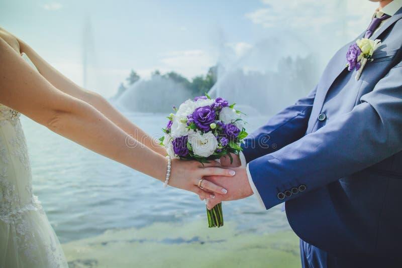 γαμήλια ανθοδέσμη στα χέρια του πρόσφατα-παντρεμένου ζεύγους στοκ φωτογραφίες
